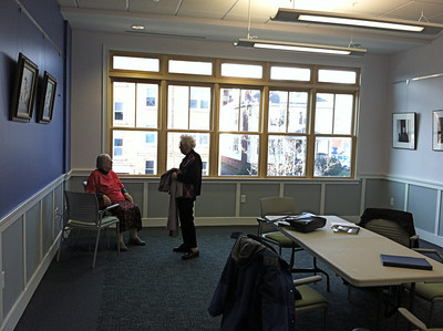 December 3, 2012. Our new room has WINDOWS!   New tables will be coming.  The photographs on right are the same portraits (of writers from this group years ago) that used to hang along the basement hall in the old location.  See separate album of photos of the NEW Senior Center.
