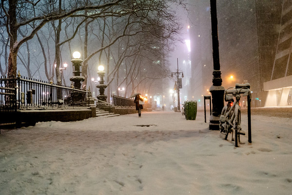 <h2>New York Winter Night - 42nd Street in the Snow</h2> - By Vivienne Gucwa   A bicycle sits covered in snow along 42nd Street in midtown Manhattan during winter storm Nemo. As the snow falls on the ground and on the beautiful fence that lines Bryant Park, a person with an umbrella makes their way through the snowfall in New York City.  ---