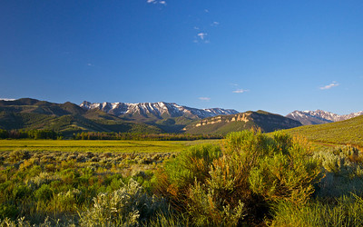 A wide mountain field lays under the mountain's shadow in northern Wyoming.