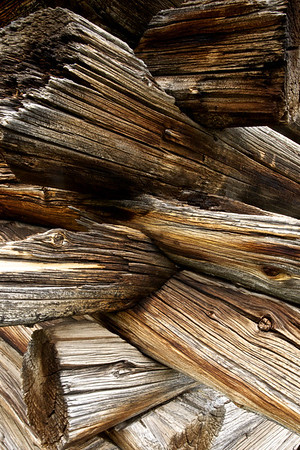 Logs of wood stacked in the corner of a cabin.