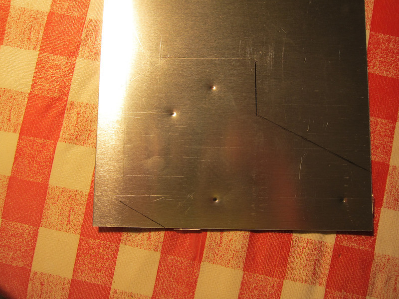 The pattern is traced onto the aluminum and using a punch I mark the places where holes will be drilled. I score along the cutout lines with a sharp knife for cleaner edges and along the fold lines for sharper angles.