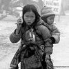 A young girl with a baby on her back in Sapa, Vietnam in January 2012