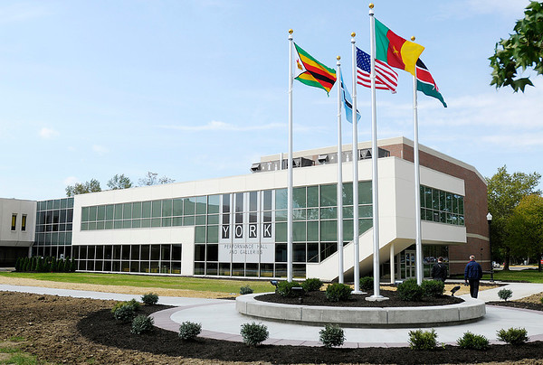 Flags of the African nations where Dr. James York and his wife Elizabeth went on medical missions fly outside the York Performance Hall during an open house on Thursday.