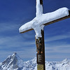 Snow covered wooden statue of Jesus on the cross in front of the matterhorn, with the inscription 'be more human'