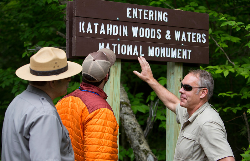 KATAHDIN WOODS AND WATERS NATIONAL MONUMENT, Maine -- 06/14/2017 - U.S. Secretary of the Interior Ryan Zinke (right) looks at the sign for the Katahdin Woods and Waters National Monument with Lucas St. Clair (center) and superintendent of Katahdin Woods Tim Hudson during a tour of the Katahdin Woods and Waters National Monument Tuesday. The visit was the start of a four-day visit to New England. Katahdin Woods and Waters National Monument is currently under  review via President Trump's Executive Order 13792, issued April 26, 2017. Ashley L. Conti | BDN