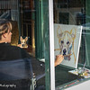 Artist painting in a window on the route