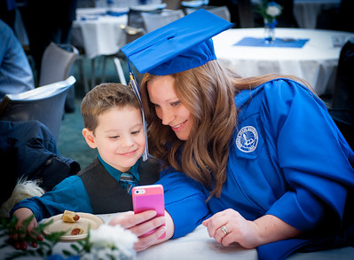 Winter 2013 commencement graduate takes a picture with relative during reception