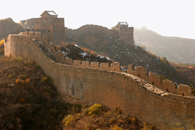 A rebuilt section of the Great Wall in the warm afternoon sunlight. You can tell if a section of the wall has likely been rebuilt (i.e. in recent decades for tourism) by the presence of intact roofs on the watchtowers.