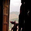 A little boy climbs through the doorway. His house has quite a view.