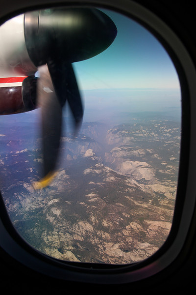 Flying over Yosemite Valley, the deep gash lined with granite cliffs. The back side of Half Dome is underneath a propeller blade facing toward the right .