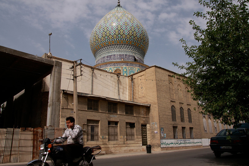 A small shrine in Shiraz. Notice the guy talking on his cellphone, on his motorcycle!
