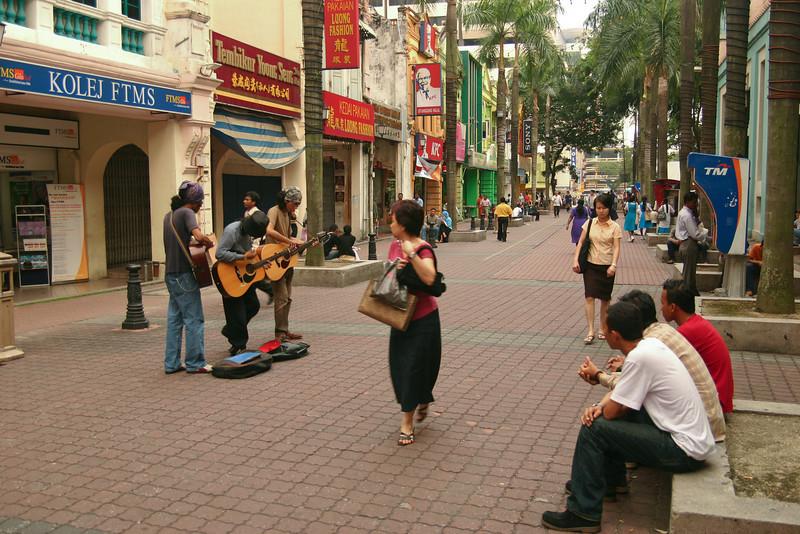 Passersby pause to watch street musicians in Kuala Lumpur, Malaysia