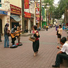 Passersby pause to watch street musicians in Kuala Lumpur, Malaysia