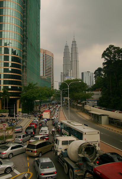 A busy Kuala Lumpur street, with the twin Petronas Towers standing tall in the distance.