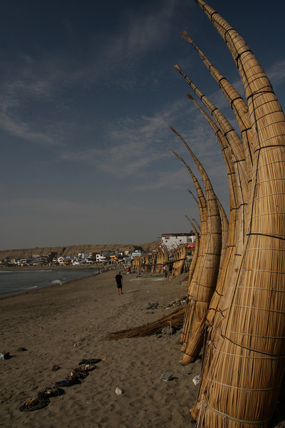 Reed boats standing up to dry on the beach in Huanchaco, Peru