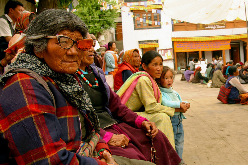 An elderly woman, probably blind in one eye, waits in the courtyard of the main Buddhist temple in Leh, Ladakh