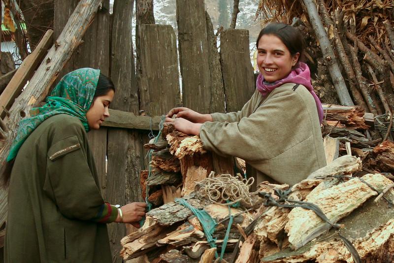 Kashmiri girls bundle firewood to take to the bazaar