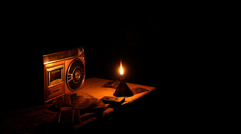 An oil lamp illuminates a pile of cassette tapes and a large family tape player in Kashmir, India