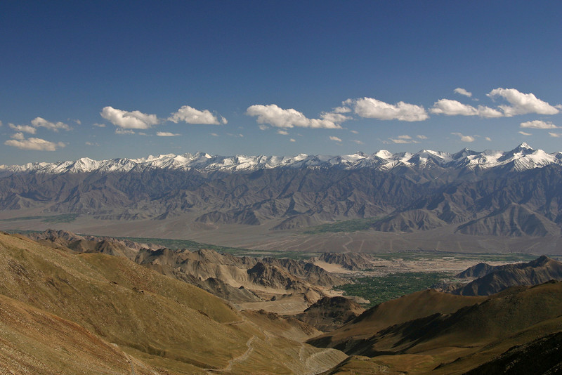 Looking south from the Khardung La across the broad Indus Valley toward the Zanskar Range in Ladakh, India. Most of the peaks visible are around 20,000 ft in elevation. The town of Leh is somewhere in the green area of the valley floor on the right.