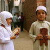 Two kids on their way to Qur'anic school. The wooden things they're holding are folding book stands.