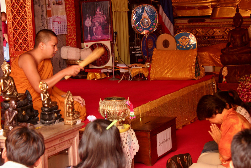 Holy water: a monk blesses worshipers in a temple by sprinkling holy water on them