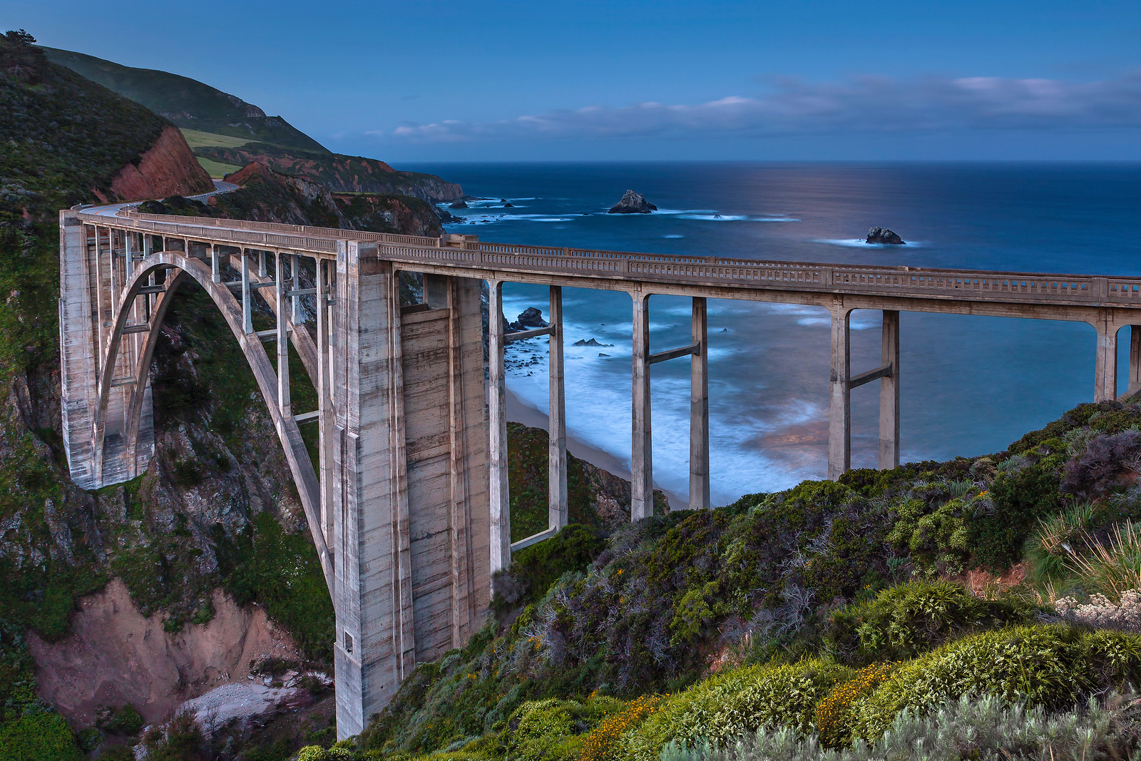 Bixby Bridge at dusk with setting moonlight on the water