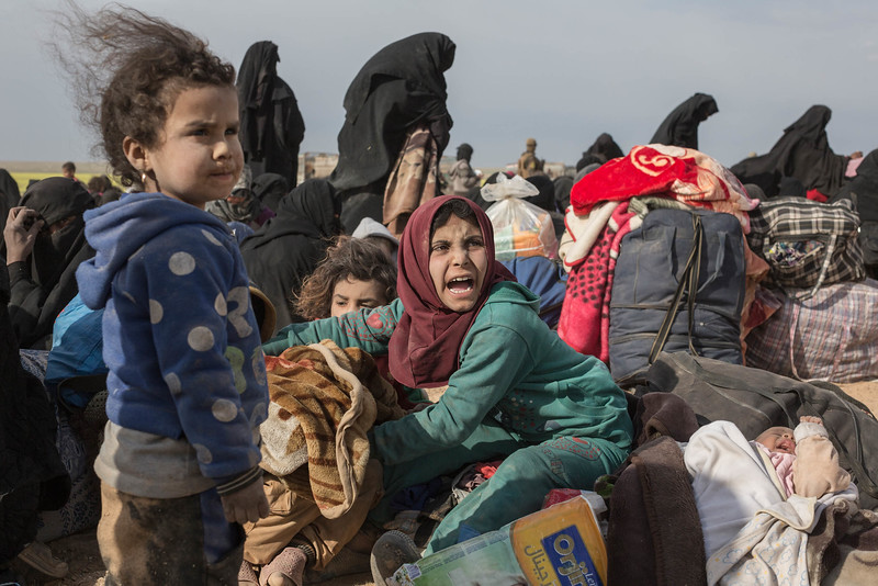 Civilians fleeing from ISIL's last remaining territory in Syria after two days of heavy fighting wait at a gathering point where before being taken to internment camp, near Baghuz, in north eastern Syria, on March 5, 2019.<br /> <br /> By the start of February 2019, the Syrian Defence Force (SDF), backed by the international coalition against ISIS, had fought ISIS into a final pocket between the Euphrates River and the Iraqi desert. The coalition had predicted the presence of some two thousand fighters and their families and a short fight to finish them off, but the fighting wouldn't end for almost two months, in which tens of thousands of civilians, fighters and their families fled ISIS's final enclave under terrible conditions. <br /> <br /> Candid picture taken during a press visit to a screening point outside Baghouz, organised by the SDF.