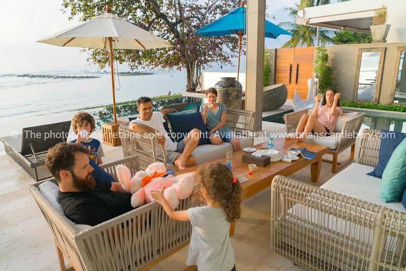 modern young families sitting around outside enjoying one and others company in warm tropical beachside environment.