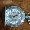 Can't really read the manufacturer.  Fits in a pocket, though, and I like a pocket watch.