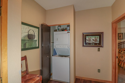 Stackable washer and dryer in the hallway, iron and ironing board.