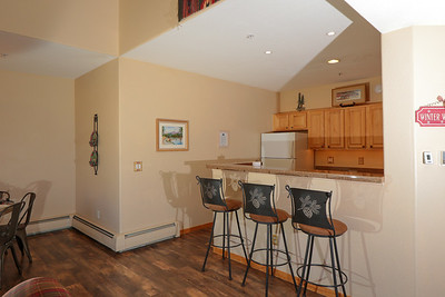 The kitchen breakfast bar with 3 bar stools.