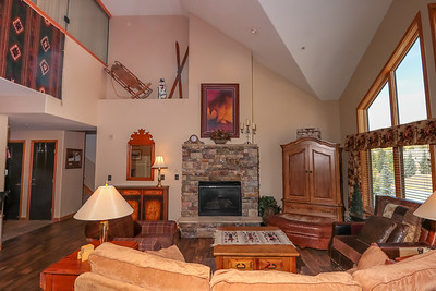 """The """"greatroom""""  dining room and  family room with large SmartTV, gas fireplace and balcony."""