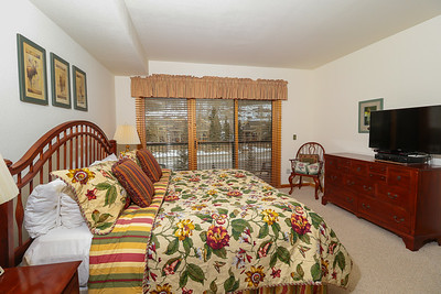 """Master bedroom with King bed, 40"""" flatscreen Smart TV, two closets, digital safe, balcony and master bathroom."""