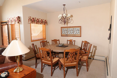 """The dining area with 60"""" dining table and 8 chairs. (Note these chairs have been replace as has the cappeting.)"""