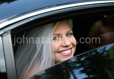 A beautiful bride looking out the window of her limousine.