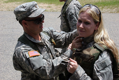 Second Lieutenent Nathan Phillips adjusts his wife Amber's IBA before firing the 240Bravo and 249 Squad Automatic Weapon Thursday at Wagner Range.