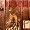 """Tobacco"", photographic illustration; three photographic elements, 2 1/4 still-life of tobacco barn, 35mm documentary portrait of Mr. Brown, and 4x5 studio still-life of Pack of Chesterfield cigarettes were collaged using Photoshop. Tobacco text designed using Adobe Illustrator placed into image using Photoshop."