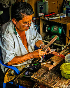 Los Dominicos, Chile- A craftsman sitting at his workbench.
