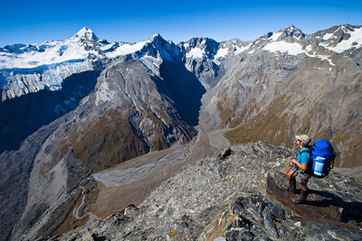 Hana on the summit of The Gladiator (2125m). From left: Sierra Range and Douglas Neve; Mount Sefton; Mount Thomson, Eagle Peak, Maunga Ma and Mount Isabel. Harper's Rock Bivouac is the black triangular boulder by the dry streambed at bottom left.