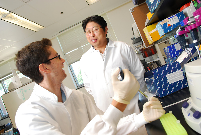 Mason biology major Clinton Enos works with mentor and cancer researcher Yuntao Wu in the National Center for Biodefense and Infectious Diseases.