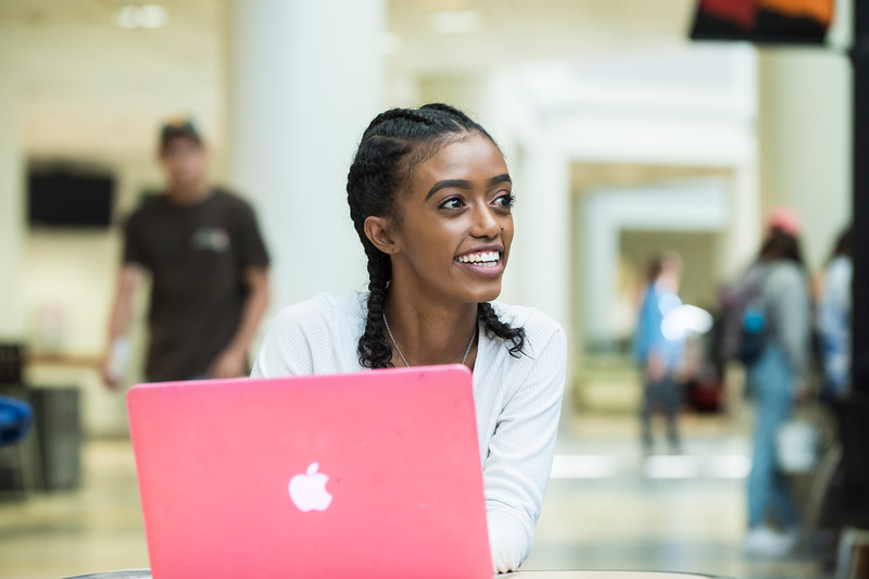 A student uses her laptop at the Johnson Center. Photo by:  Ron Aira/Creative Services/George Mason University