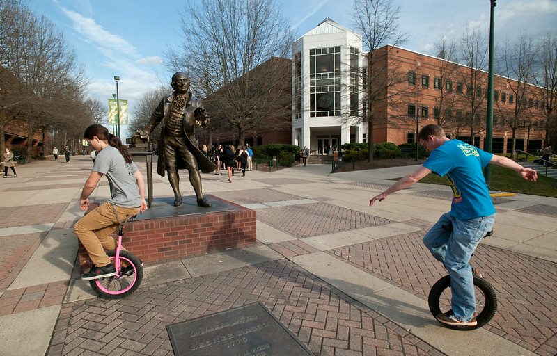 Zach Price (L),  a Sophomore in the S-CAR program, and Scott Cooper, a Freshman in Film and Video Studies, ride unicycles near the Mason Statue and the Johnson Center at Fairfax Campus. Photo by Alexis Glenn/Creative Services/George Mason University