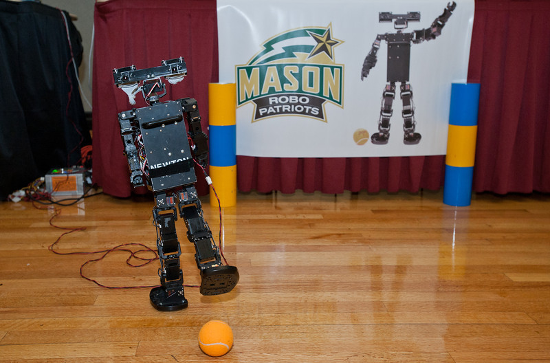 """Newton"" a robot constructed by Mason's Robo Patriots Club demonstrates his kicking abilities at Volgenau School's Engineers Day in Dewberry Hall at Fairfax Campus. Photo by Alexis Glenn/Creative Services/George Mason University"
