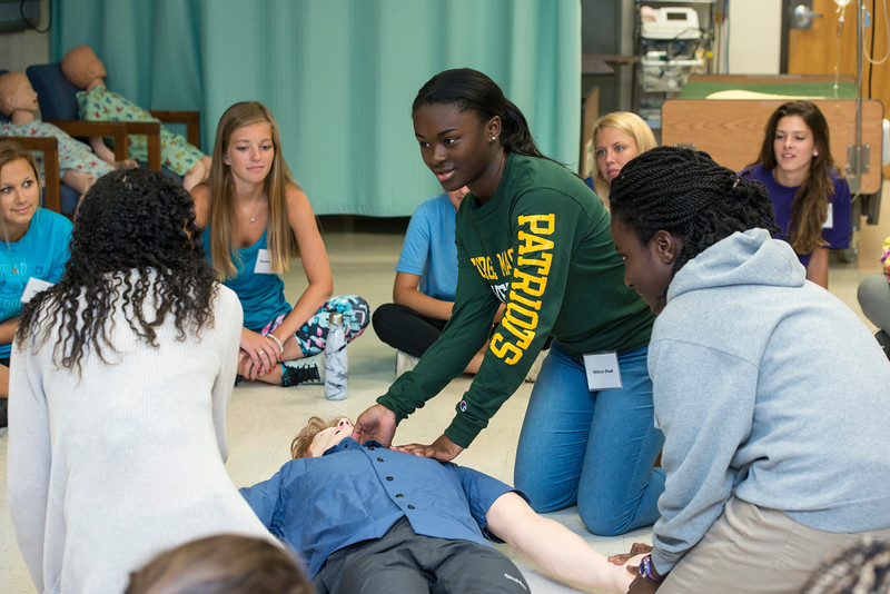 High school students attending the Nursing Camp practice giving CPR with a simulation and learn about what the paramedics will do once they arrive on the scene.  Photo by Bethany Camp/Creative Services/George Mason University