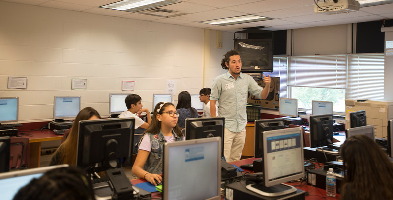 Recent graduate in game and design, Shipley Owens, uses vintage video games to help teach students at Stonewall Middle School in Manassas, VA.  Photo by Jamie Rogers/Creative Services/George Mason University