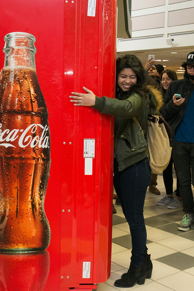 Students hug a Coke machine in the Johnson Center to get a free drink. Photo by: Bethany Camp / Creative Services / George Mason University