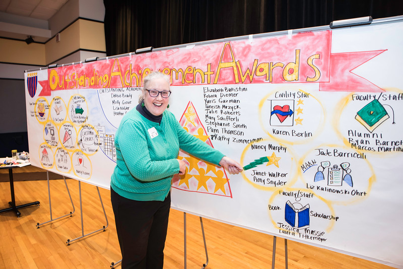 Janet Walker, Life/Work Connections Manager, Human Resources/Payroll stands next to some artwork about her award during the 2016 Outstanding Achievement Award.  Photo by Ron Aira/Creative Services/George Mason University