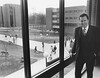 Dr. Johnson posing for a picture inside of Student Union Building I on the Fairfax Campus of George Mason University. Outside the window, the Fenwick Library Tower is the structure on the left and Robinson Hall A is the structure to the right. This picture was taken during Dr. Johnson's first academic year as university president. 1979.  Copyright George Mason University.