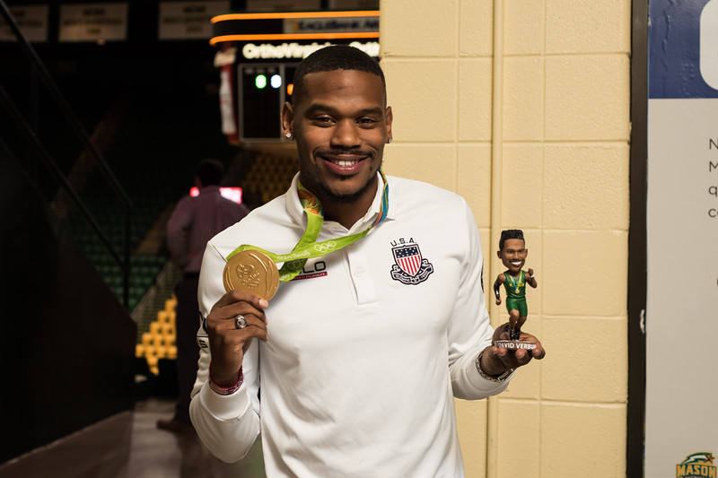 Mason alumnus and Olympic gold medalist David Verburg shows off his medal and bobble head during the men's basketball game against La Salle on Sat. Feb. 4, 2016.  Photo by Bethany Camp/Creative Services/George Mason University