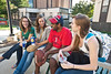 Students (L to R) Tierney Kulik, Alison Strope, Nick Sharma, and Ellie Brady talk on a bench outside at Fairfax Campus.